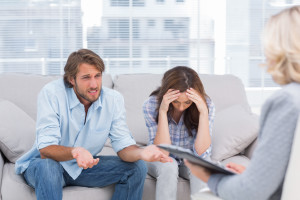 Young couple sit on the couch of the therapist and the woman is crying